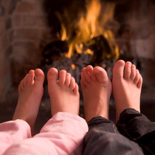 Children warming feet by fireplace